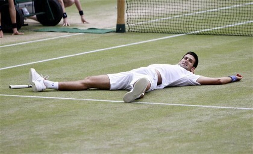 Serbia's Novak Djokovic celebrates after defeating Spain's Rafael Nadal in the men's singles final at the All England Lawn Tennis Championships at Wimbledon, Sunday, July 3, 2011. (AP Photo/Alastair Grant)
