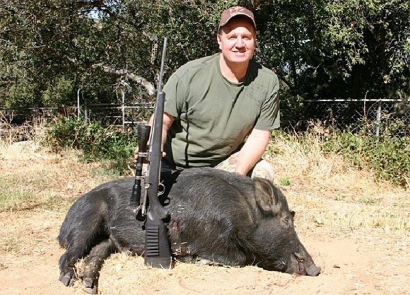 John Ogle poses with the 241-pound boar he shot with his daughter's rifle north of El Capitan Reservoir this week.