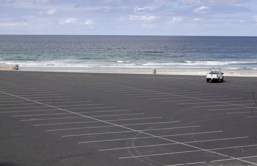 A single lifeguard truck is the only vehicle in a closed parking lot at Seaside Reef in Cardiff on April 5.
