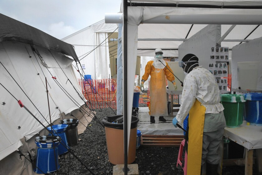 A health worker begins the disinfection process after a shift in the high-risk area of the Doctors Without Borders Ebola treatment center in Paynesville, Liberia.