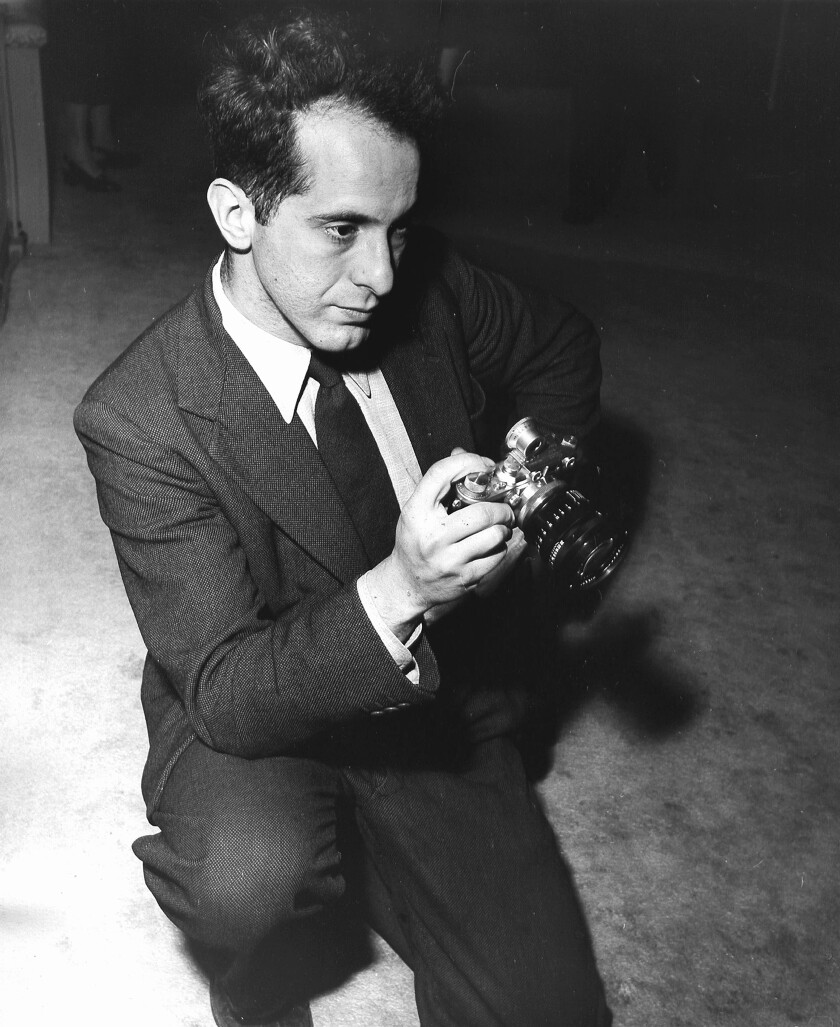 American photographer Robert Frank holding a prewar Leica camera, 1954.