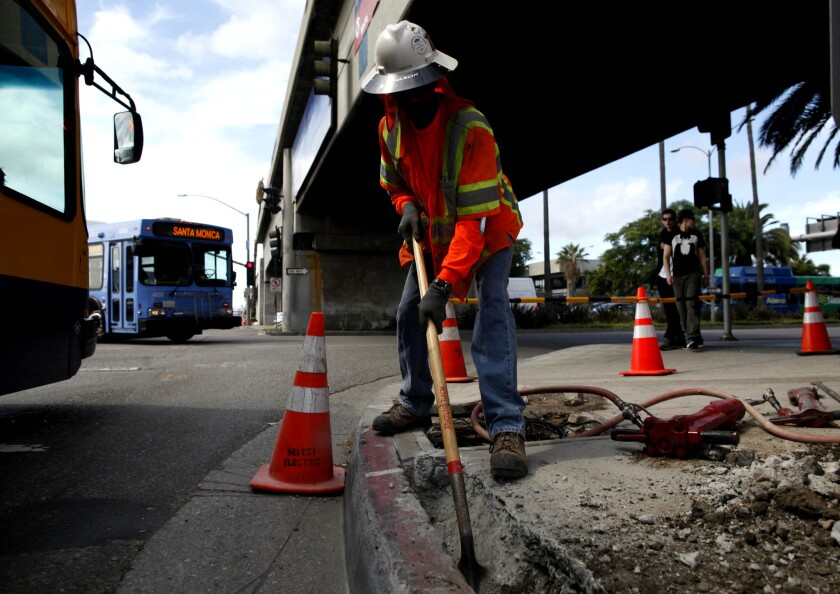 A construction worker cleans out a trench on a roadway project at Los Angeles International Airport. The White House has proposed a budget that increases passenger fees to raise funding for airport improvement projects.