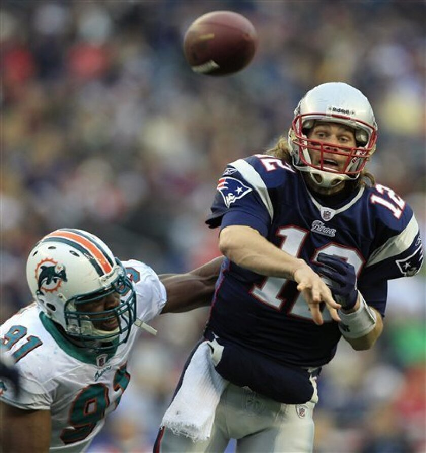 New England Patriots quarterback Tom Brady, right, passes as he is pressured by Miami Dolphins linebacker Cameron Wake during the second quarter of an NFL football game in Foxborough, Mass., Sunday, Jan. 2, 2011. (AP Photo/Charles Krupa)