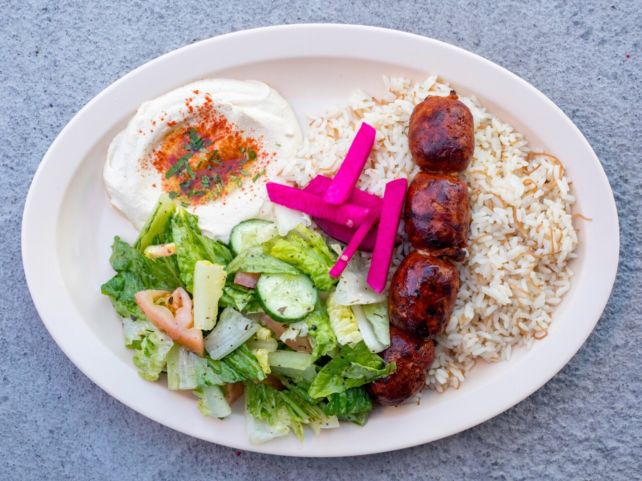 Chorizo kebab served with rice, Lebanese salad and hummus at X'tiosu Kitchen in Boyle Heights.
