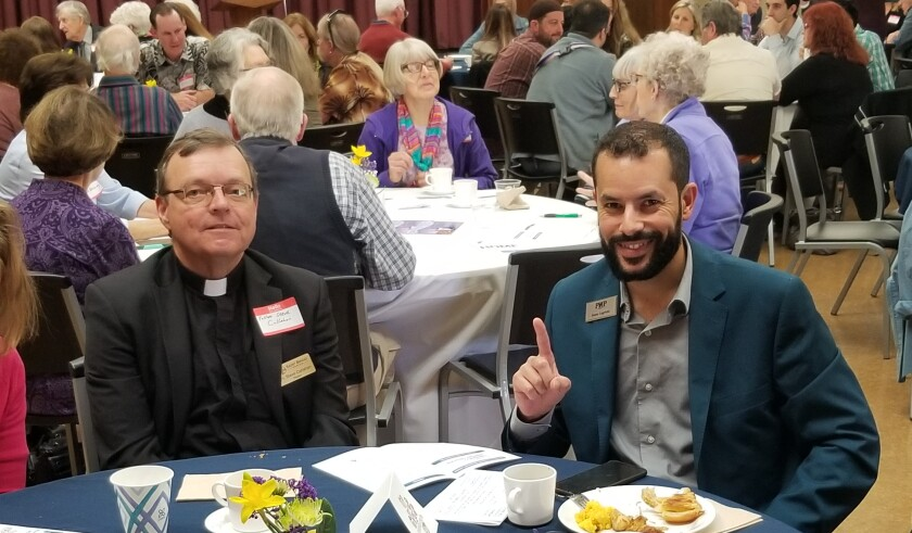 Father Steve Callahan and Issam Lagrichi are among the Interfaith Coalition Prayer Breakfast attendees.