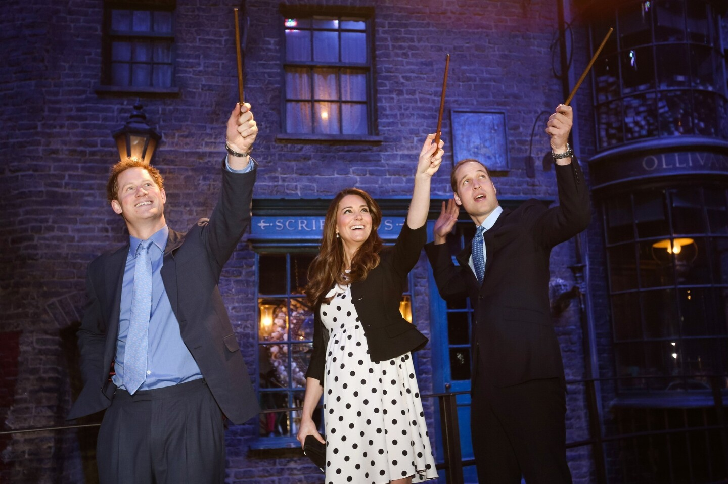 """Prince Harry, Catherine, Duchess of Cambridge, and Prince William raise their wands on the set used to depict Diagon Alley in the """"Harry Potter"""" films during the inauguration of Warner Bros. Studios Leavesden on April 26, 2013, in London."""