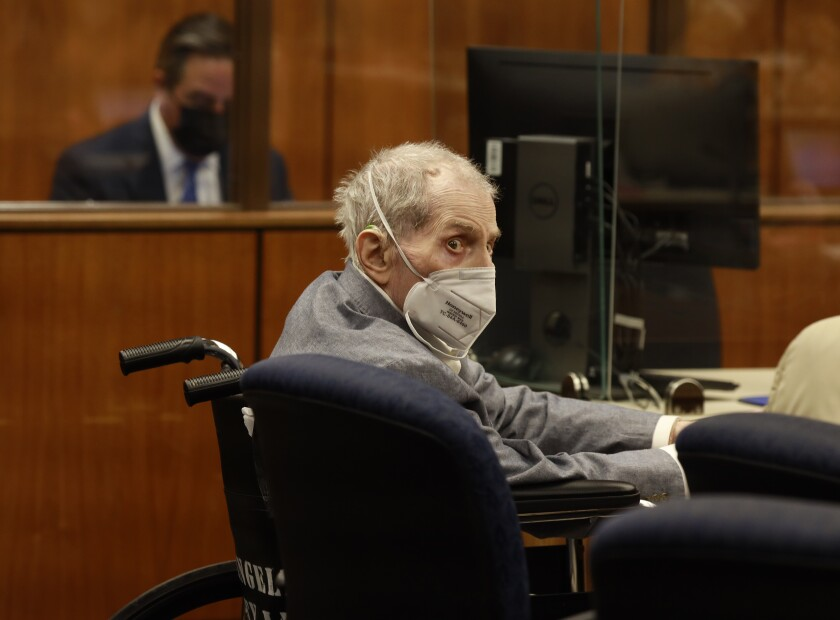 Robert Durst sits in a wheelchair wearing a mask in a courtroom.