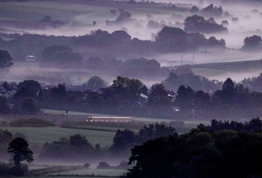 A regional train runs through the fog covered landscape in the Taunus region near Wehrheim early Tuesday, Sept. 28, 2021. (AP Photo/Michael Probst)