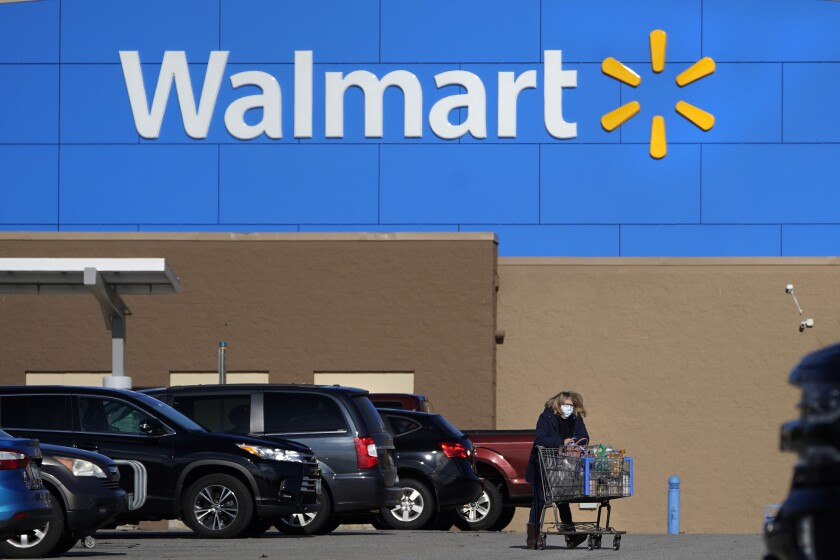 FILE - In this Nov. 18, 2020 file photo, a woman, wearing a protective face mask due to the COVID-19 virus outbreak, wheels a cart with her purchases out of a Walmart store, in Derry, N.H. Walmart, the world's largest retailer, said Friday, May 14, 2021 that it won't require vaccinated shoppers or workers to wear a mask in its U.S. stores, unless state or local laws say otherwise. Vaccinated shoppers can go maskless immediately, the company said. Vaccinated workers can stop wearing them on May 18. (AP Photo/Charles Krupa, File)