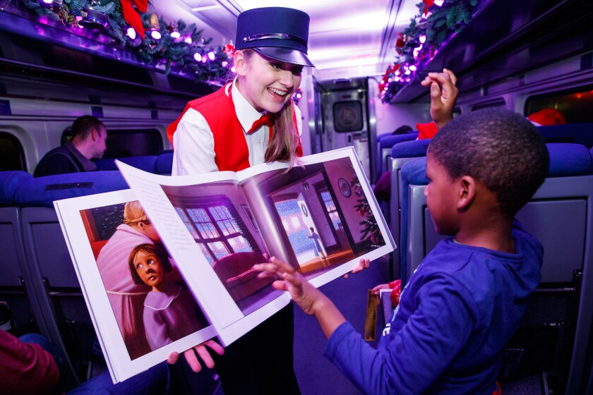 "A woman in a train conductor outfit holds open ""The Polar Express"" for a boy riding the train inspired by the book."