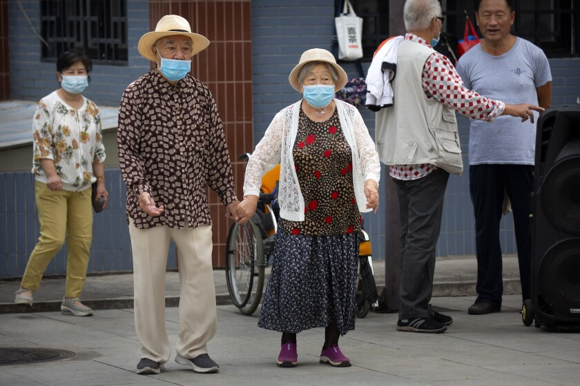 An elderly couple wearing face masks to protect against the coronavirus walks at a public park in Beijing, Saturday, Sept. 12, 2020. Even as China has largely controlled the outbreak, the coronavirus is still surging across other parts of the world. (AP Photo/Mark Schiefelbein)