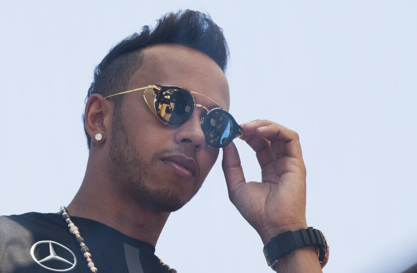 Mercedes driver Lewis Hamilton of Britain adjusts his sunglasses during a television interview at the Monaco racetrack, in Monaco, Wednesday, May 20, 2015. The Formula One Grand Prix will be held on Sunday. (AP Photo/Gero Breloer)
