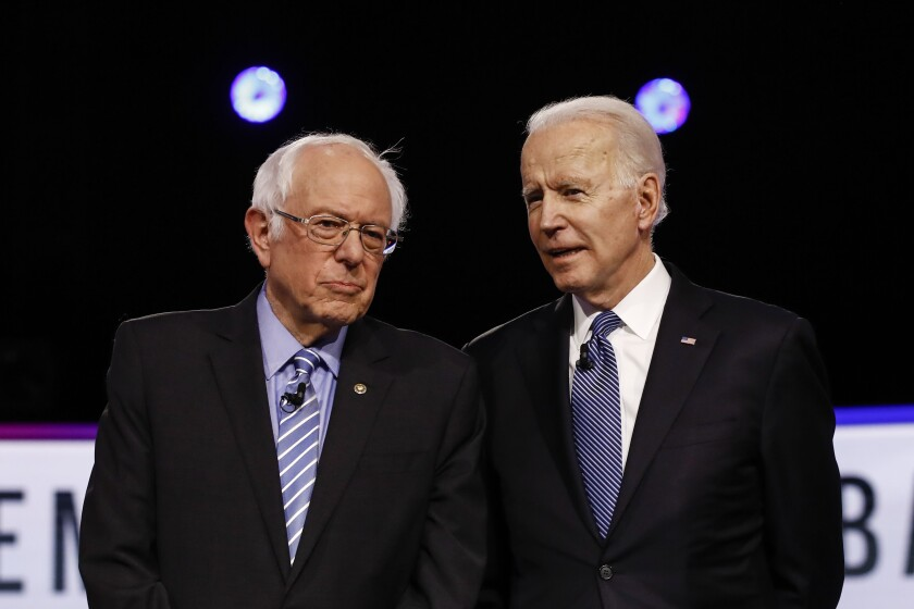 Democratic presidential candidates Sen. Bernie Sanders and former Vice President Joe Biden talk before a debate in Charleston, S.C., on Feb. 25.