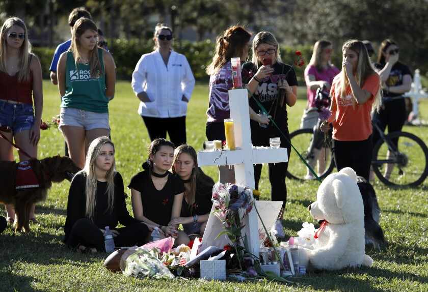 Students gather at a memorial in Pine Trails Park in Parkland, Fla., in honor of the Marjory Stoneman Douglas High School shooting victims.