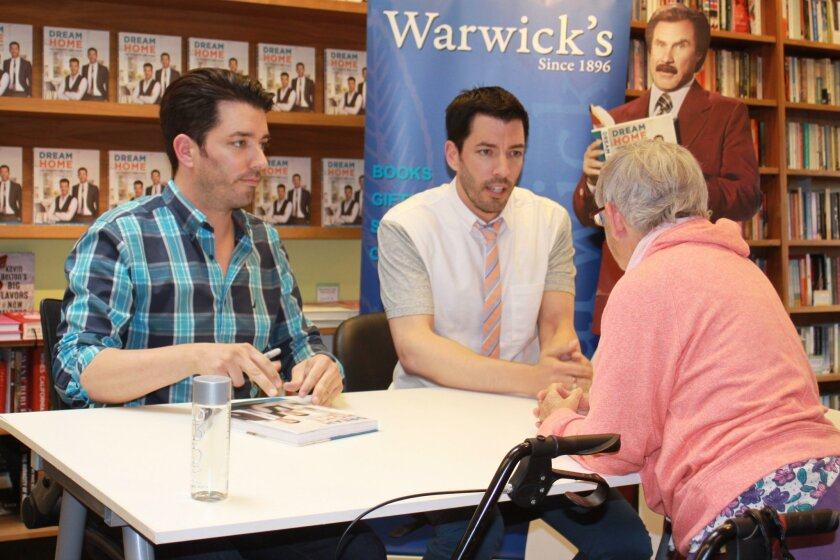 Drew and Jonathan (or is it Jonathan and Drew?) Scott sign a fan's book and answer questions.