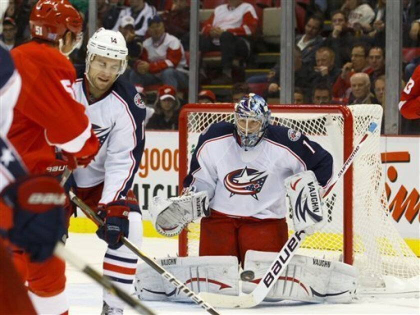 Columbus Blue Jackets goalie Steve Mason (1) makes a save on a shot by Detroit Red Wings center Valtteri Filppula, left, of Finland, as Columbus Blue Jackets defenseman Grant Clitsome (14) defends during the second period of an NHL hockey game in Detroit, on Friday, Oct. 21, 2011. (AP Photo/Rick Os