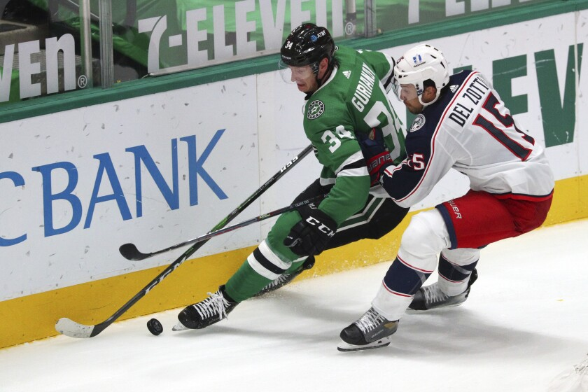 Dallas Stars right wing Denis Gurianov (34) and Columbus Blue Jackets defenseman Michael Del Zotto (15) battle for the puck int he second period during an NHL hockey game on Thursday, April 15, 2021, in Dallas. (AP Photo/Richard W. Rodriguez)