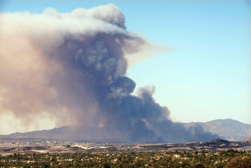 A plume of smoke is seen from a fire on Camp Pendleton Saturday afternoon. This photo was taken from a hilltop in Vista. Photo by Anthony Carrasco.