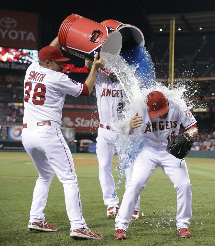 Los Angeles Angels relief pitcher Huston Street, right, is doused with liquid by Joe Smith, left, and Mike Trout after a baseball game against the Minnesota Twins, Wednesday, July 22, 2015, in Anaheim, Calif. The Angels won 5-2 and Street earned his 300th career save. (AP Photo/Jae C. Hong)