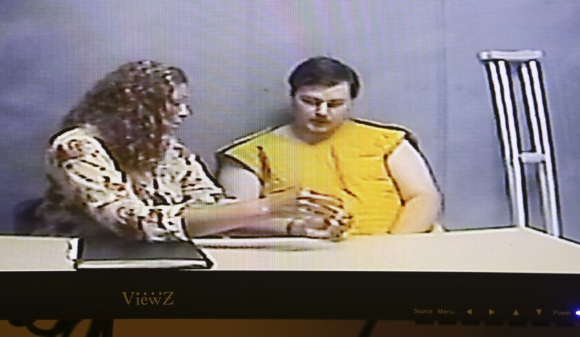 Assistant public defender Lindsay Garner, left speaks to her client Alexander Ken Jackson, 20, as he appears for his initial court appearance via video conference at the Linn County Courthouse in Cedar Rapids, Iowa, on Wednesday, June 16, 2021. Jackson has been charged with three counts of first-degree murder, and is in custody at the Linn County Jail. (Jim Slosiarek/The Gazette via AP)