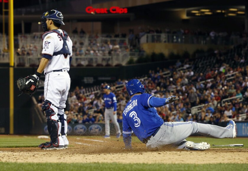 Toronto Blue Jays pinch-runner Ezequiel Carrera, right, scores the go-ahead run behind Minnesota Twins catcher Kurt Suzuki on a hit by Troy Tulowitzki during the 11th inning of a baseball game Thursday, May 19, 2016, in Minneapolis. The Blue Jays won 3-2 in 11 innings. (AP Photo/Jim Mone)