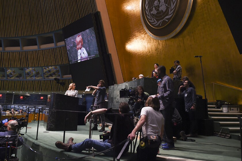 """Madam Secretary"" star Tea Leoni, at the podium, and crew on stage inside the United Nations. The show was given rare permission to film in the General Assembly hall for its episode ""Ghost Detainee."""