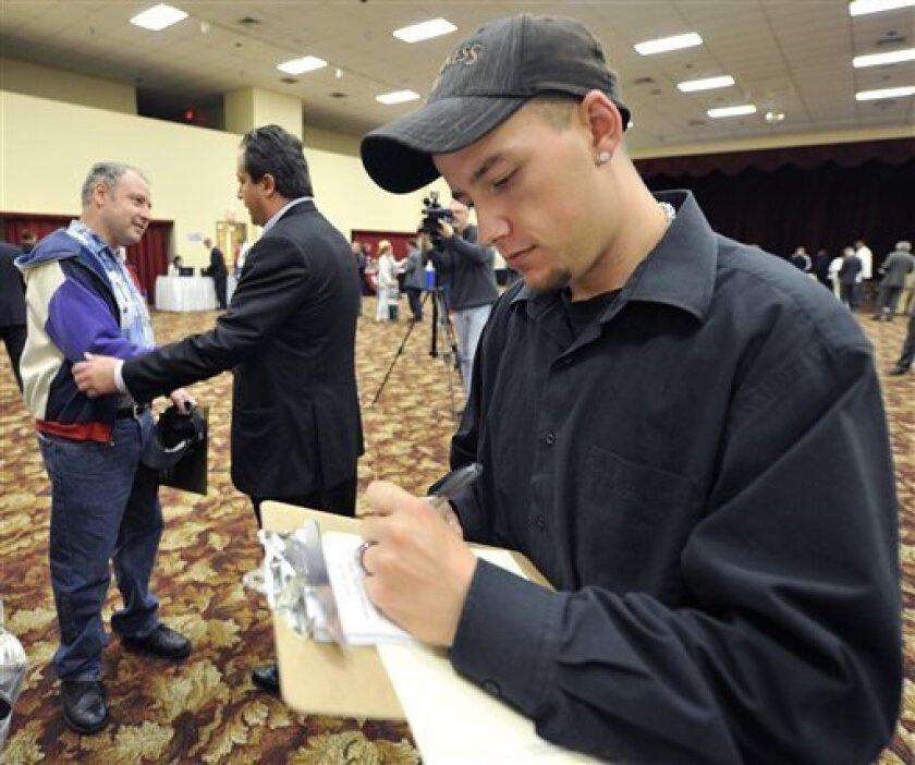 In this Oct. 5, 2010 photo, Timothy King of Rockton, Ill., fills out some paperwork as Kevin Numbers, left talks with Scott Lee Cohen, Independent Candidate for Governor of Illinois during a job fair in Rockford, Ill. Applications for unemployment benefits fell last week for the fourth time in five weeks, a sign that layoffs are declining. (AP Photo/Jim Prisching)