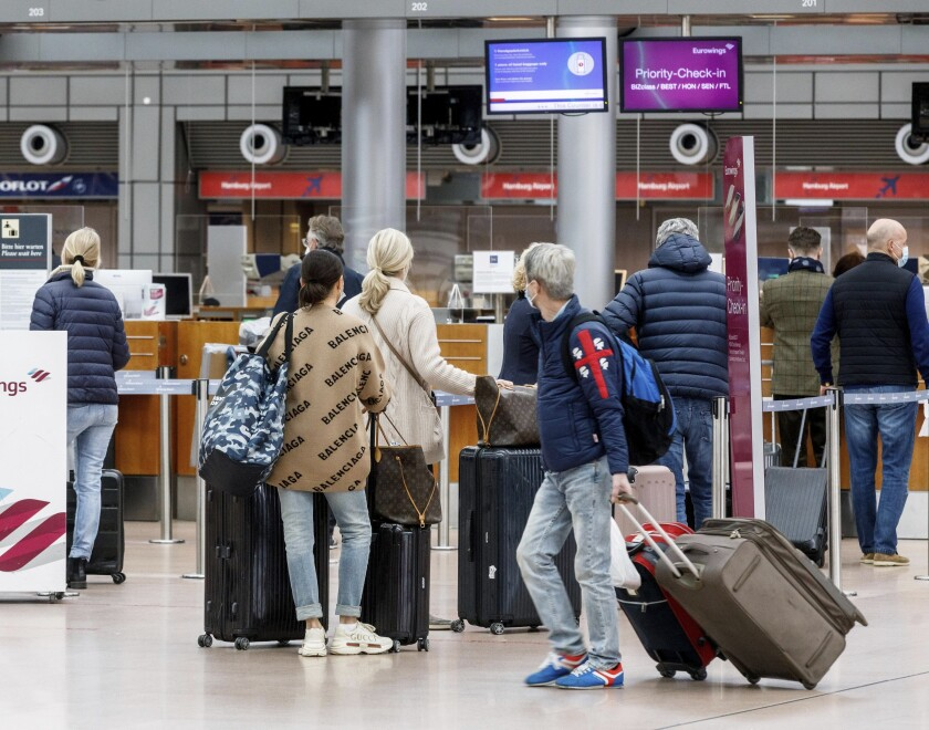 Passengers check in at Hamburg Airport, Germany, for flight Eurowings EW 7588 to Palma de Mallorca on Sunday, March 14, 2021. Due to sharply falling Corona infection figures, the German government lifts travel restrictions for Mallorca, Spain's most important tourism island. (Markus Scholz/dpa via AP)