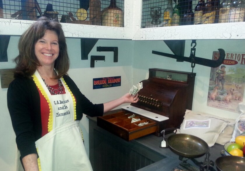 The Temecula Valley Museum recently renovated its 'Touch History' children's area, making the inside of its exhibits accessible to visitors as well as interactive. Shown is museum manager Tracy Frick playing with the Temecula General Store exhibit's antique cash register.