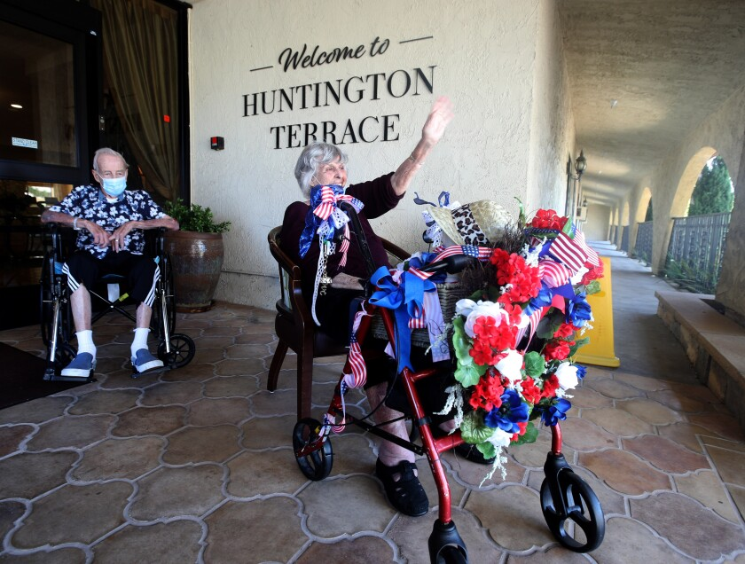Senior Bev Ison, 79, right, from Huntington Terrace Senior Living waves as the Sycamore Creek Community Charter School Senior Cheer Parade drives by their location in Huntington Beach on Saturday.