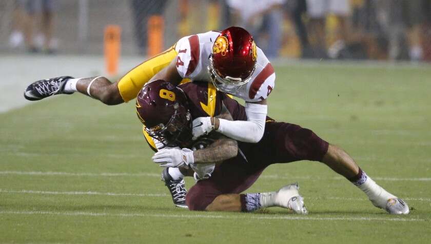 USC cornerback Isaiah Langley tackles Arizona State receiver D.J. Foster during a game on Sept. 26, 2015.