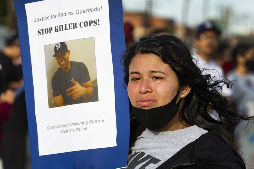 "A woman holds up a poster with a photo of Andres Guardado that says ""Stop killer cops!"""
