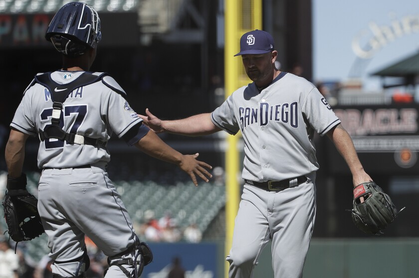 Padres closer Kirby Yates celebrates with catcher Francisco Mejia on Wednesday after earning his seventh save of the season in a 3-1 victory over the Giants.