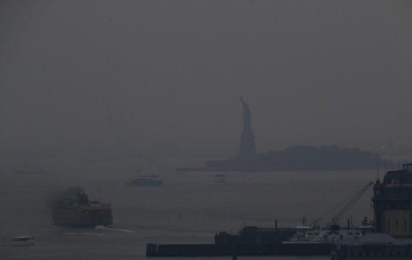El ferry Staten Island sale de una terminal en Manhattan a través de una capa de humo con la Estatua de la Libertad de fondo, el martes 20 de julio de 2021 en Nueva York. (AP Photo/Julie Jacobson)