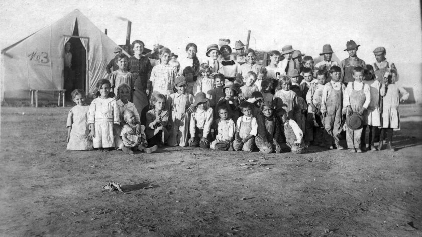This 1914 photo provided by the Denver Public Library, Western History Collection, shows children and some adults posing for a photo at camp Ludlow in south central Colorado.  Two women and 11 children died in a fire at the camp during a battle between the Colorado National Guard and striking coal
