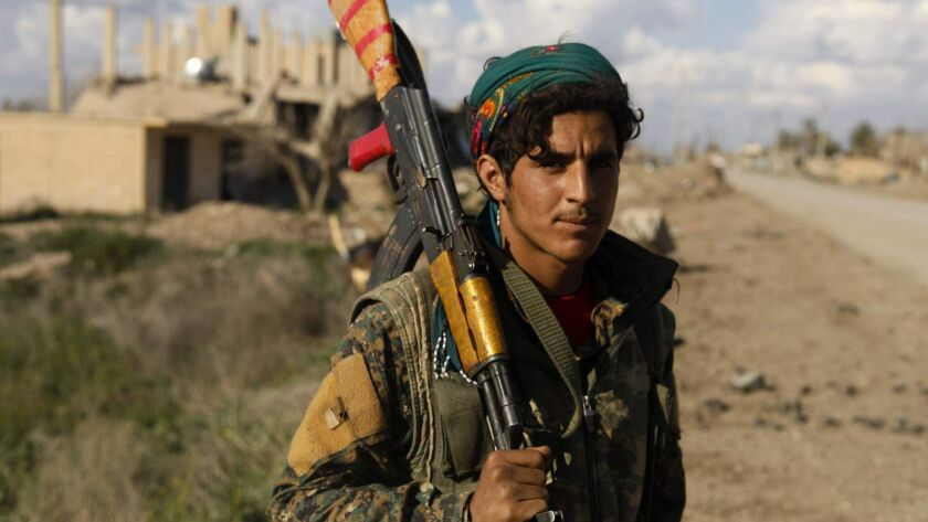 A fighter with the U.S.-backed Kurdish militia known as the Syrian Democratic Forces in the village of Baghouz on Feb. 19, 2019. The group has been fighting the remnants of Islamic State's self-declared caliphate in eastern Syria.