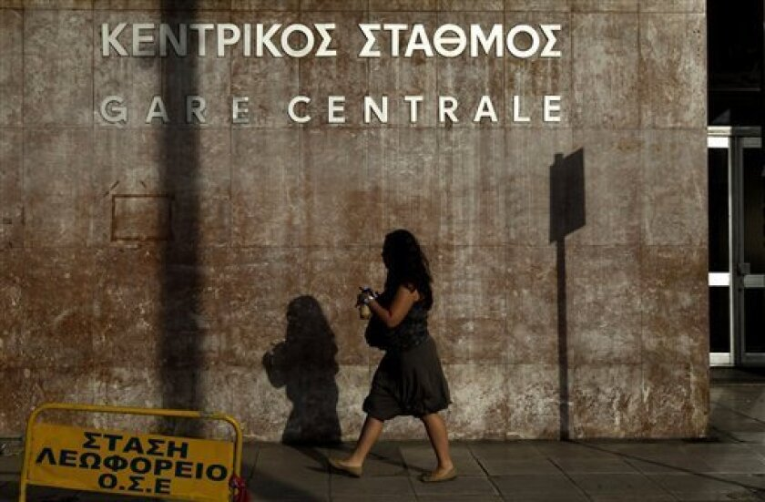 A woman passes outside the central train station of Athens during a strike, on Thursday, June 9, 2011. All train services in Greece have been suspended after state railway employees launched a series of strikes against planned reforms. Workers at state-run companies walked off the job in a series of work stoppages Thursday to protest the government's privatization plan in Greece's renewed push to meet the terms of its international bailout.(AP Photo/Petros Giannakouris)