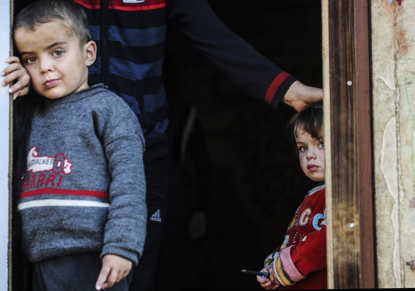 Syrian refugees look out from their shelter in Hatay, Turkey.