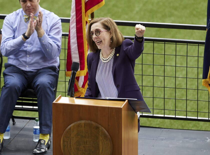 FILE - In this Wednesday, June 30, 2021, file photo, Oregon Gov. Kate Brown pumps her fist while announcing the end of the state's COVID-19 restrictions in Portland, Ore. Brown said Friday, Aug, 13, she will send up to 1,500 National Guard troops to hospitals around the state to assist healthcare workers who are being pushed to the brink by a surge of COVID-19 cases driven by the Delta variant. (AP Photo/Craig Mitchelldyer, File)
