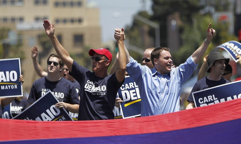 Mayoral candidate Carl DeMaio, right, holds hands aloft with partner Johnathan Hale as they march in the San Diego LGBT Pride Parade in July.