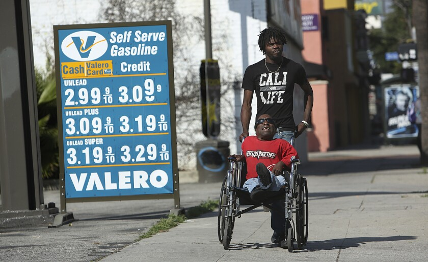 Vincent Cowart, top, and his brother Eddie Peterson of Los Angeles, make their way past a sign showing the prices of gas at a Valero gas station on Van Nuys Boulevard in Van Nuys. Wholesale gas prices rose 6 to 10 cents in California after a large refinery explosion.