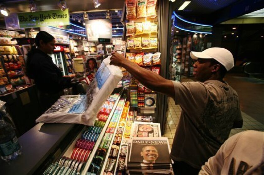In this Nov. 5, 2008 file photo, Ralston Montaque buys thirty copies of The New York Times from Hudson News in New York. Many newspapers are making preparations with increased press runs and special sections for the historic inauguration of the nation's first black president. (AP Photo/Mark Lennih
