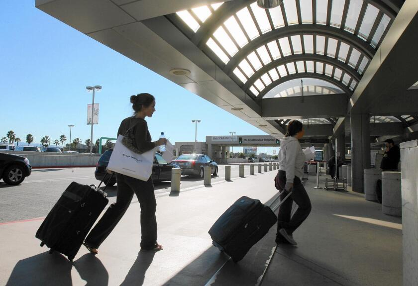 Travelers make their way into John Wayne Airport in this file photo. The airport estimates it will lose as much as $50 million in revenue in the 2020 fiscal year as a result of a sharp drop in passenger traffic and other airport business due to the coronavirus outbreak.