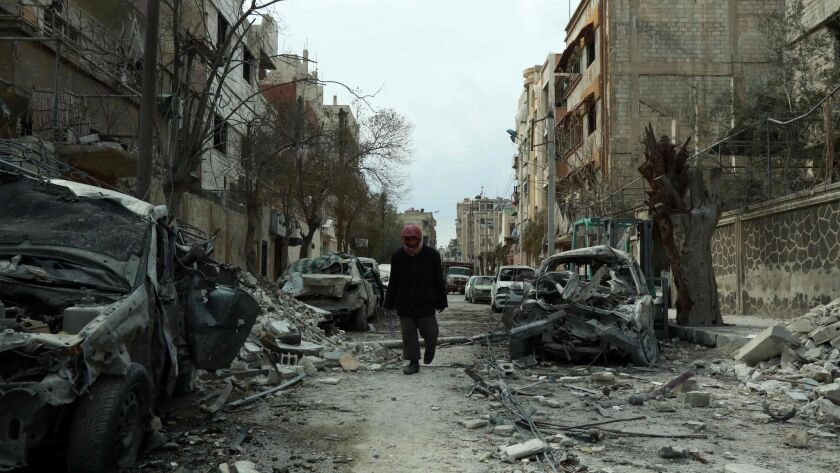 A Syrian man walks next to damaged buildings Sunday after airstrikes in the Syrian rebel-held town of Duma.