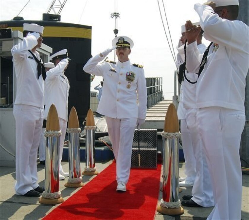 In this Aug. 3, 2012 photo provided by the U.S. Navy, Cmdr. Michael P. Ward II, center, is saluted during the change-of-command ceremony for the nuclear submarine USS Pittsburgh at the Naval Submarine Base New London, in Groton, Conn.  Ward was relieved of his command in August 2012 after he faked