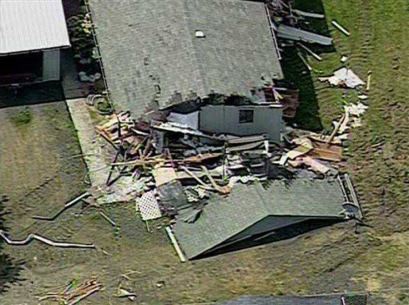 This frame grame from aerial video footage provided by KOMO-TV shows damage allegedly caused by Barry Alan Swegle, a man angry at his neighbors who went on a rampage in a bulldozer, damaging four homes, knocking one off its foundation and cutting power to thousands of people, authorities said, Friday, May 10, 2013 in Port Angeles, Wash. Swegle was booked into the Clallam County Jail for investigation of malicious mischief following the incident. (AP Photo/KOMO-TV) SEATTLE OUT, DAILY MAIL OUT, N