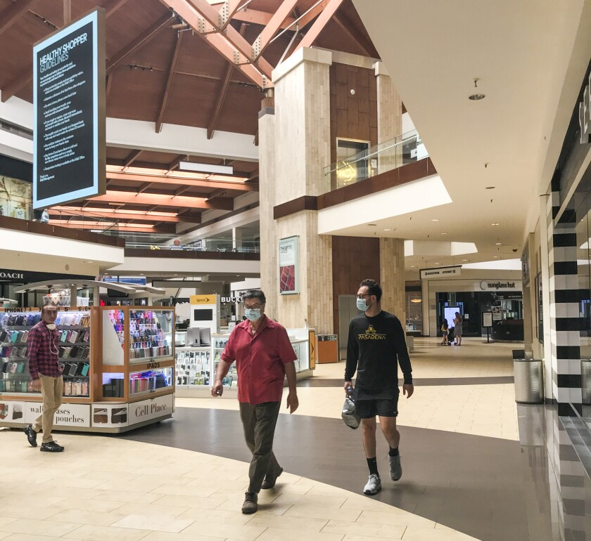 Shoppers walk around Orange County's Brea Mall, which reopened Tuesday.