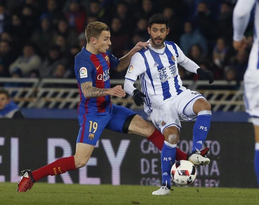 El delantero de la Real Sociedad Carlos Alberto Vela (d) pelea un balón con el defensa del FC Barcelona Lucas Digne durante el partido de ida de cuartos de final de la Copa del Rey, que se juega en el estadio de Anoeta de San Sebastián. EFE