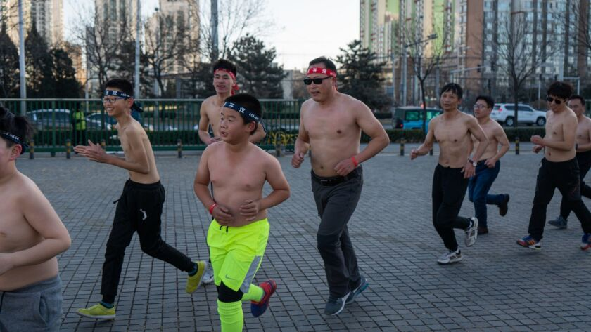 Boys and trainers of the Real Man Training Club run through a Beijing Park in December. Founder Tang Haiyan, center, in sunglasses, also runs with the group.