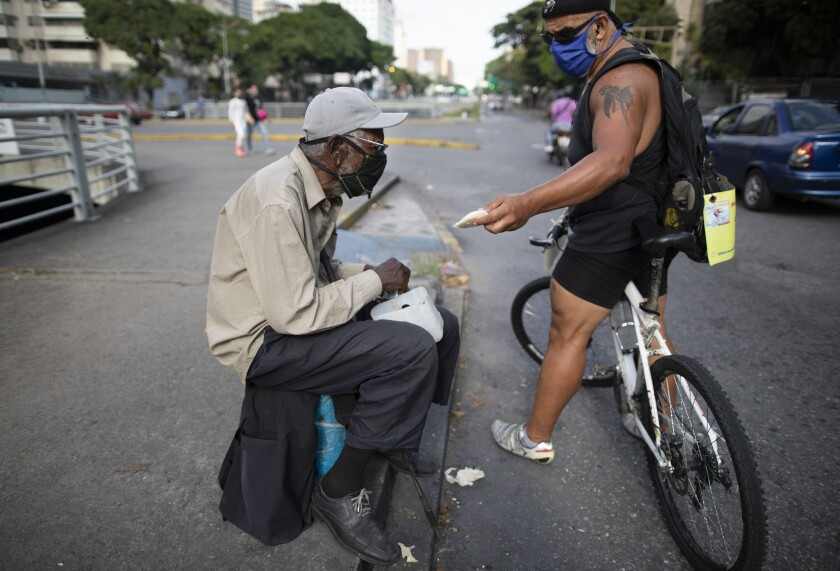 Andres Burgos, a 55-year-old publicist, gives a package of arepas or corn flour patties to a man begging for money at a traffic light in Caracas, Venezuela, Tuesday, Oct. 20, 2020. Burgos hands out his homemade arepas from the seat of his bicycle to needy children, adults and the elderly. He calls it BiciArepazo, which translates roughly as Bike Arepas. (AP Photo/Ariana Cubillos)